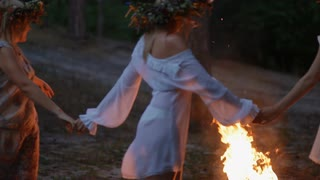women-with-wreath-on-the-head-dance-in-the-circle-around-the-fire-holding-hands-beautiful-slavic-tradition-on-kupala-holiday_nlz0bbxae__S0000